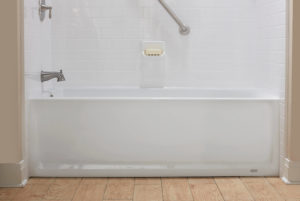 A white bathtub with white tile walls, brushed nickel fixtures, and a safety grab bar.